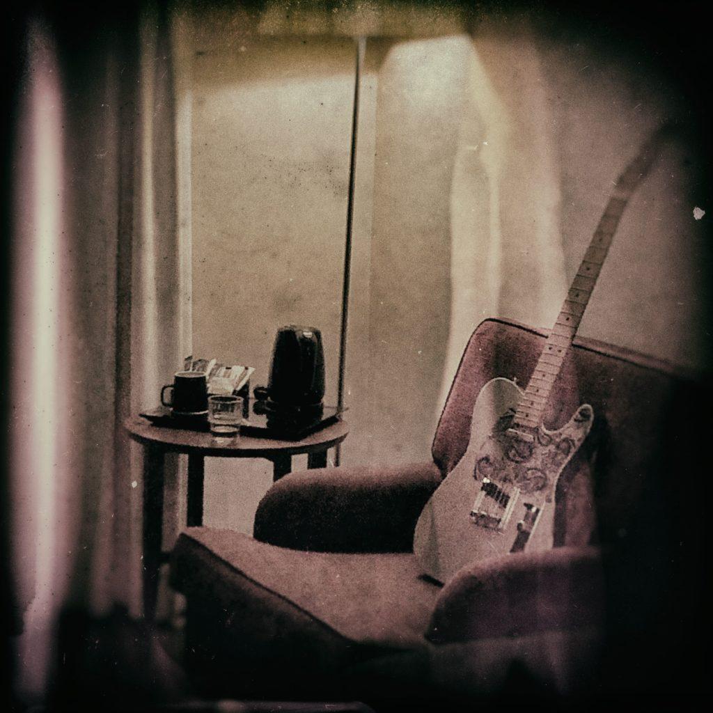 En gitarr i en fåtölj i ett hotellrum